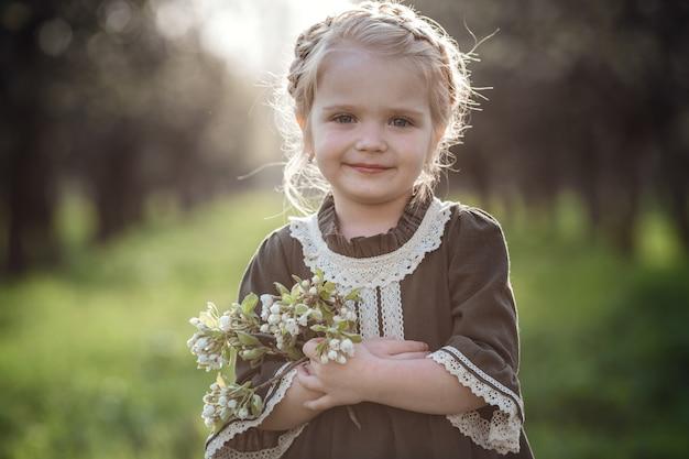 Mała śliczna dziewczyna w sukience w ogrodzie kwiat. cute dziewczynka 3-4 lat gospodarstwa kwiaty nad naturą. portret wiosny. aromatyczny kwiat i koncepcja retro vintage.