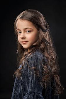 Mała śliczna dziewczyna w szarości sukni na czarnym tle.