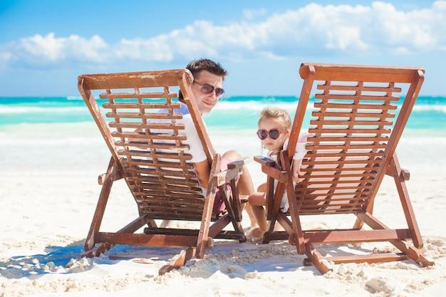 Mała śliczna dziewczyna z jej młodym tata obsiadaniem na plażowych drewnianych krzesłach patrzeje kamerę