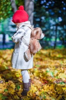 Mała śliczna dziewczyna z niedźwiadkowym plecakiem chodzi w jesień lesie na pięknym słonecznym dniu