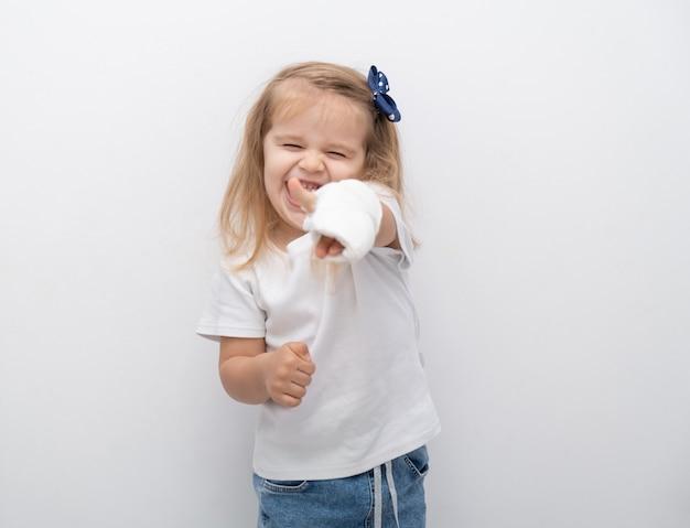 Mała śliczna dziewczyna z ręką w gipsie, pokazując klasę na białym tle.