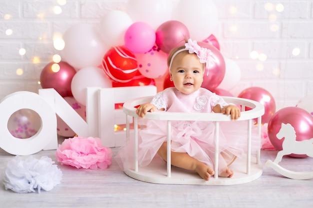 Mała śliczna dziewczynka siedzi z literami jeden i balonami, pierwszy rok, urodziny, wakacje