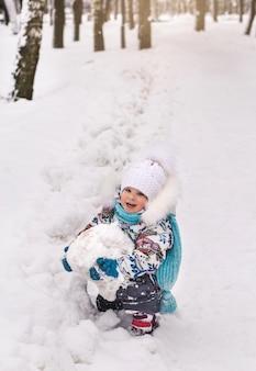 Mała śliczna dziewczynka trzyma dużą śnieżkę zimą w parku