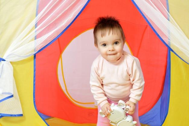Mała śliczna dziewczynka trzyma zabawkę na rękach w małym domu