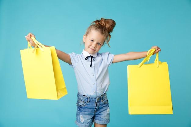 Mała śliczna i zabawna dziewczyna trzyma duże jasne kolorowe żółte papierowe torby w niebieskim studio.