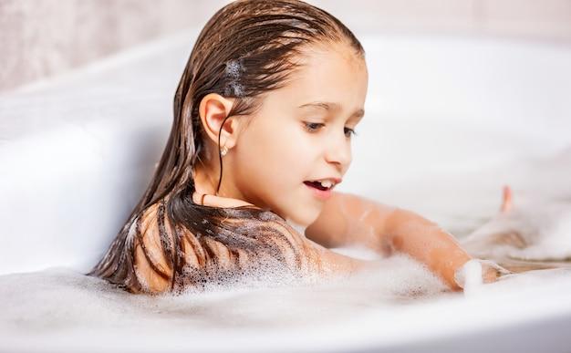 Mała śliczna kaukaska dziewczyna kąpie się w wannie z pianką.