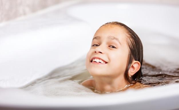 Mała śliczna kaukaska dziewczynka kąpie się w wannie z pianką i bawi się podczas kwarantanny w domu