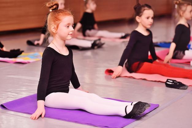 Mała śliczna rudowłosa dziewczyna balerina wykonuje ćwiczenia rozciągające w szkole baletowej