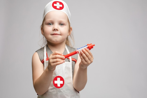 Mała śliczna śmieszna dziewczyna bawić się będący ubranym lekarka munduru mienia zabawki strzykawkę patrzeje kamerę
