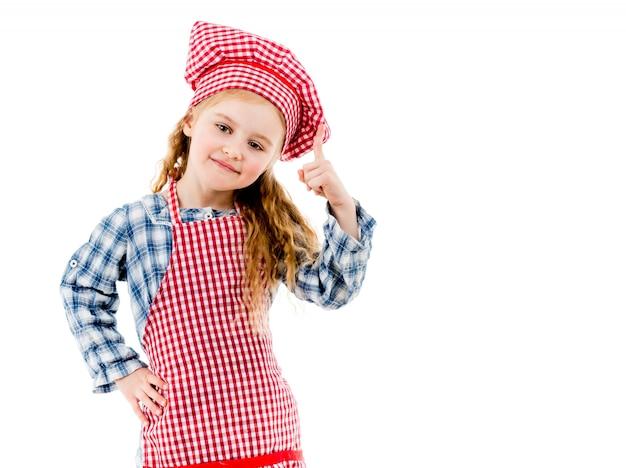 Mała śliczna szef kuchni dziewczyna wskazuje w górę odosobnionego na białym tle