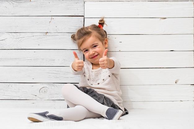Mała śliczna szkolna dziewczyna siedzi na białym drewnie