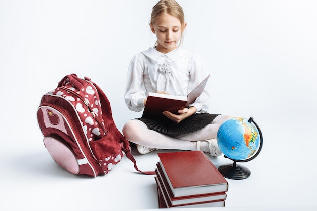 Mała śliczna szkolna dziewczyna siedzi z książkami i kulą ziemską, czyta książkę