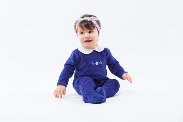 Mała śliczna urocza uśmiechnięta dziewczyna z łękiem w włosianym obsiadaniu w studiu pozuje na białym tle