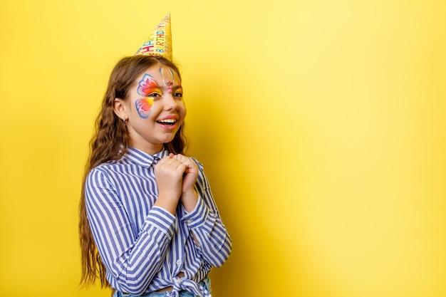 Mała śliczna urodzinowa dziewczyna w imprezowej czapce z pozowaniem na białym tle na żółtej ścianie