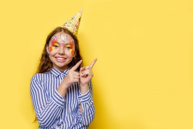 Mała śliczna urodzinowa dziewczyna w partyjnej nakrętce z wskazywać pod ona odosobnionego na kolorze żółtym