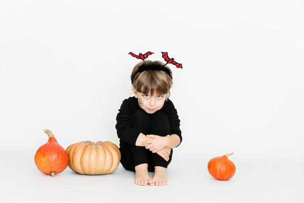 Mała słodka dziewczyna w czarnych ubraniach wśród dyni świętowanie halloween