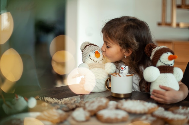 Mała słodka dziewczynka bawi się bałwankami na drutach, je pierniki i pije kakao z piankami