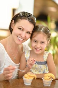 Mała słodka dziewczynka je lody z matką