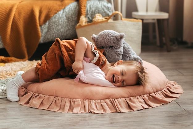 Mała słodka dziewczynka maluch bawi się poduszkami w pokoju dziecięcym