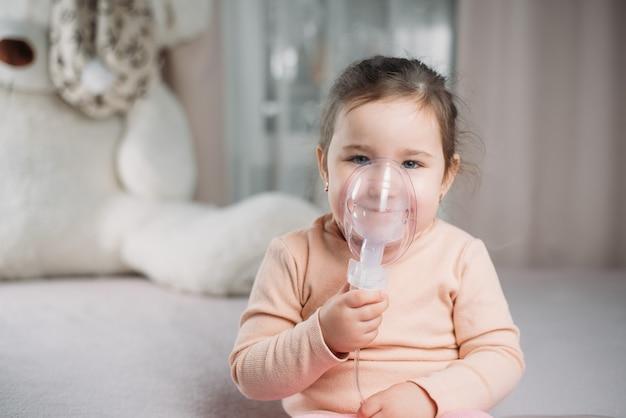 Mała słodka dziewczynka siedzi na łóżku w sypialni i sama robi inhalację