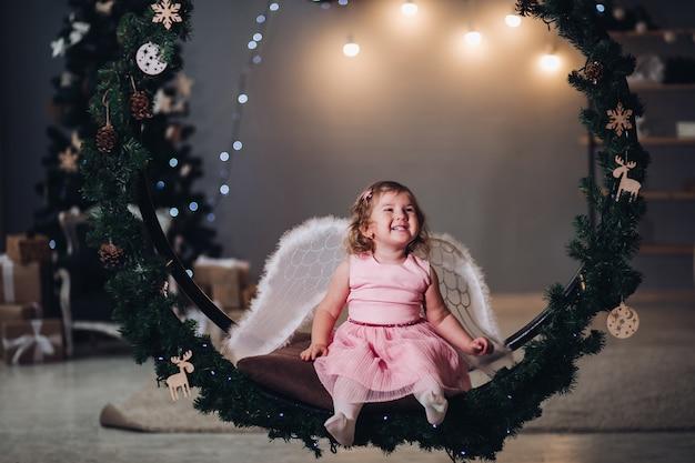 Mała słodka dziewczynka w sukience z anielskimi krzyżami siedzi w dużej okrągłej scenerii ze świerkowych gałęzi