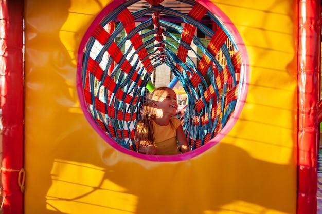 Mała słodka dziewczynka wspina się przez jasny długi tunel na placu zabaw z kolorowym miękkim sprzętem ciesząc się letnimi wakacjami