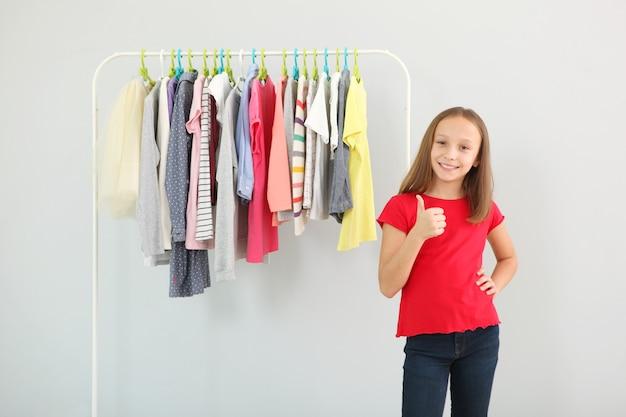Mała słodka dziewczynka wybiera ubrania w garderobie