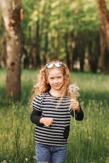 Mała śmiejąca się dziewczynka zbiera w lecie białe mlecze w parku. pionowy