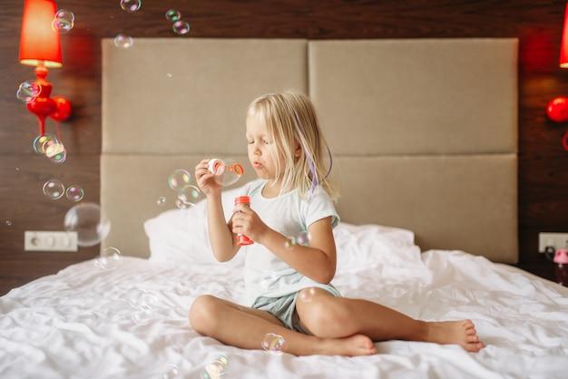 Mała śmieszna dziewczyna, leżąc w łóżku i dmuchanie baniek. prawdziwie beztroskie dzieciństwo, szczęśliwy czas