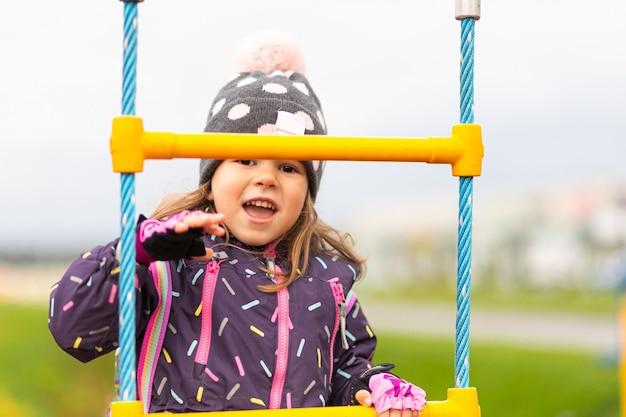Mała śmieszna dziewczyna w ciepłej kurtce, kapeluszu wspina się po schodach na placu zabaw w parku miejskim.
