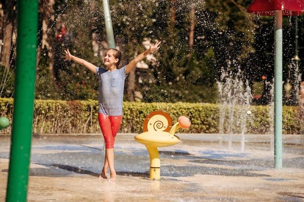 Mała śmieszna dziewczyna w plamy na wodnym placu zabaw w parku latem. wypoczynek dla dzieci w aquaparku, wodna przygoda