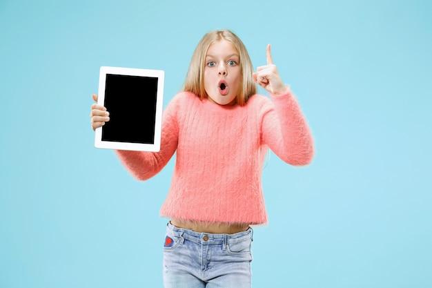 Mała śmieszna dziewczyna z tabletem na niebieskiej przestrzeni
