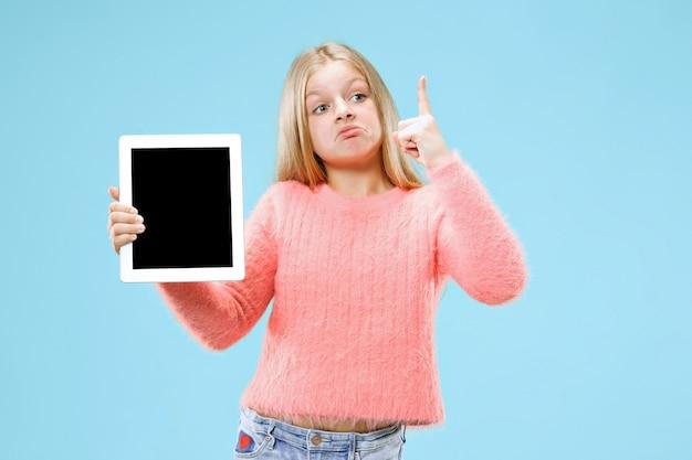 Mała śmieszna dziewczyna z tabletem na niebieskim tle studia. pokazuje coś i wskazuje w górę