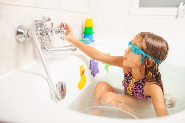 Mała śmieszna dziewczynka w niebieskich okularach kąpielowych patrzy w kamerę i uśmiecha się uroczo, wylewając na siebie wodę z prysznica
