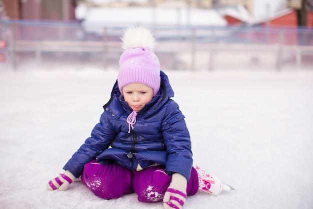 Mała smutna dziewczyna siedzi na lodzie z łyżwy po upadku