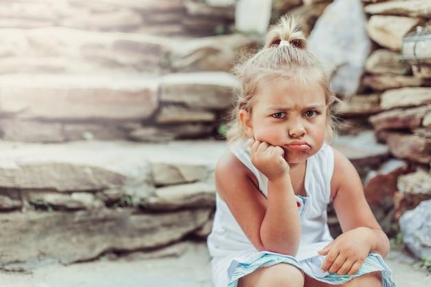 Mała smutna dziewczyna siedzi na skale