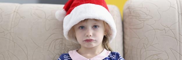 Mała smutna dziewczynka siedzi na kanapie w kapeluszu świętego mikołaja
