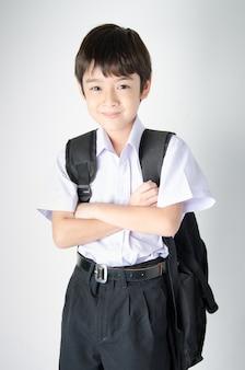 Mała studencka chłopiec w mundurze na białym tle