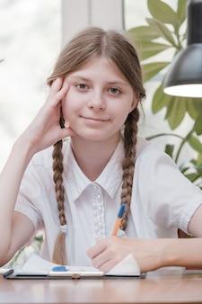 Mała studencka dziewczyna studiuje w szkole. domowe hobby. uśmiechnięta dziecko dziewczyna obraz w domu. kształcić się przez nauczyciela vs uczyć się i uczyć w domu z rodzicami. młoda dziewczyna odrabianiu lekcji.