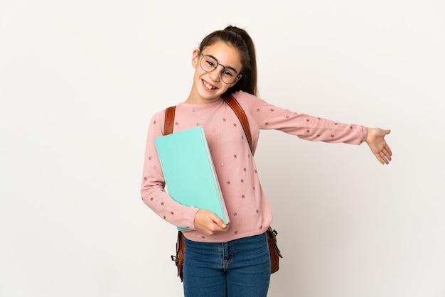Mała studentka na białym tle, wyciągając ręce do boku, zapraszając do przyjścia