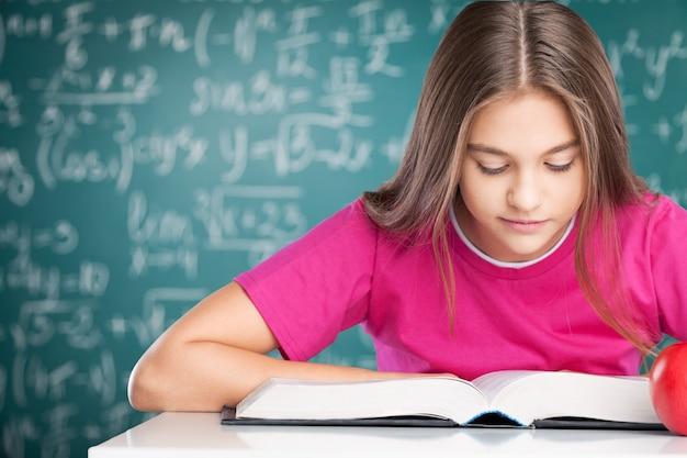 Mała studentka studiująca na tle