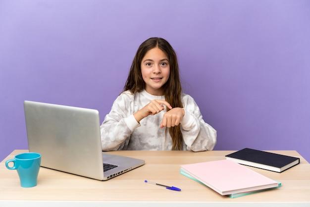 Mała studentka w miejscu pracy z laptopem na fioletowym tle robi gest spóźnienia