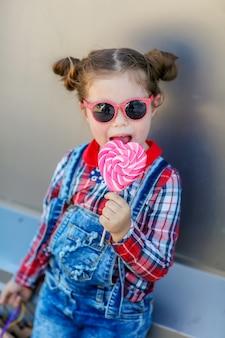 Mała stylowa dziewczyna w okularach przeciwsłonecznych i dwa warkoczach na głowie