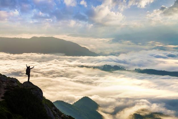 Mała sylwetka turysty z plecakiem na skalistym zboczu góry z podniesionymi rękami