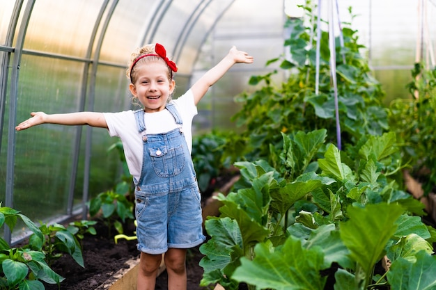 Mała szczęśliwa blondynka w szklarni z rękami w górze raduje się koncepcją ogrodniczą pielęgnacji roślin