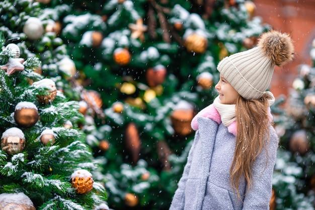 Mała szczęśliwa dziewczyna blisko jedliny gałąź w śniegu dla nowego roku.