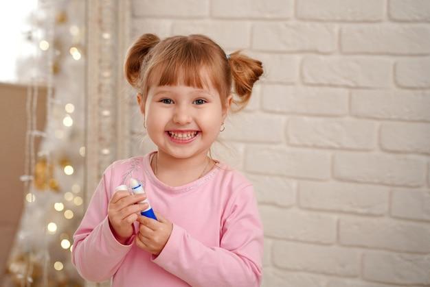 Mała szczęśliwa dziewczyna cieszy się pierwszym doświadczeniem malowania ust szminką