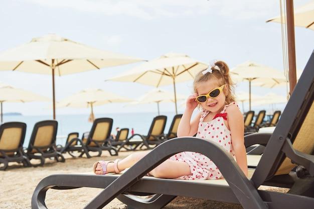 Mała szczęśliwa dziewczyna na leżakach nad morzem