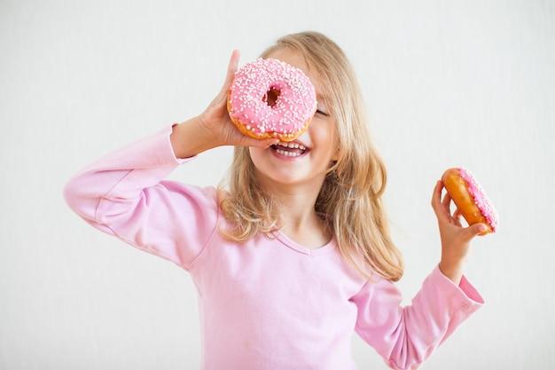 Mała szczęśliwa dziewczyna o blond włosach bawi się i degustuje pączki z różowym lukrem podczas obchodów chanuka