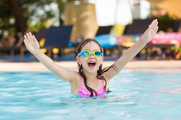 Mała szczęśliwa dziewczyna pływa w plenerowym basenie z nurkowymi szkłami w pogodnym letnim dniu
